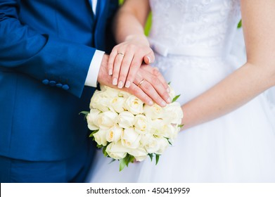 bride and groom hands and bouquet.Beautiful couple with a bouquet of white roses.Gestures, emotions, hands,