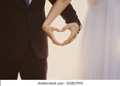 the bride and groom hands forming heart shape a symbol of love