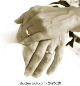 Bride and groom hands over wedding dress