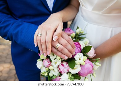 Bride and groom hands with wedding rings and bridal bouquet