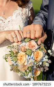 bride and groom hands with weddingrings showing power fist