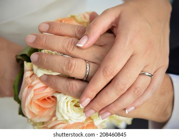 bride and groom hands with White gold rigs on the wedding bouquet background