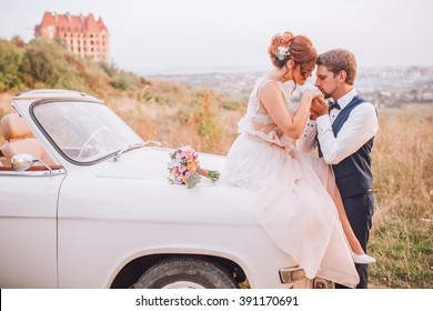 The bride and groom have fun behind the wheel of retro car. Wedding