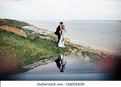 Bride and groom have fun walking across the green field along the sea