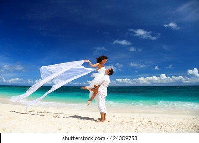 Bride and groom having fun on white sandy tropical beach. Beach wedding concept