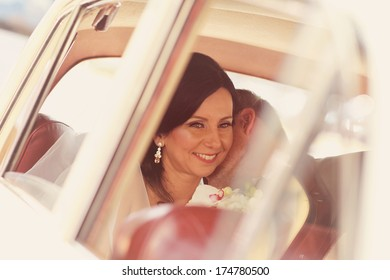 Bride and groom having fun in a retro car
