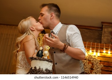 Bride and groom having fun at the wedding party, kissing each other after cutting the delicious wedding cake. Indoors