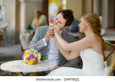 Bride and groom having an ice cream in outdoor cafe
