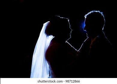 A bride and groom are having their first dance. silhouette of a couple dancing