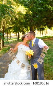 A bride and groom hold a banner of burlap that reads thank you so they can use it later for their thank you cards.