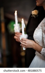 Bride and groom hold candles on wedding ceremony at church