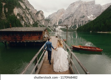 Bride and groom hold each other hands walking along the bridge over the lake in Italian Dolomites