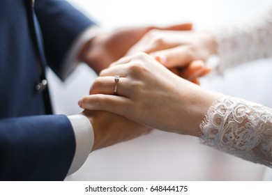 The bride and groom hold hands close-up, hands of lovers at the wedding ceremony, engagement ring on the finger of the bride, the groom holds the bride by the hand, a touching moment of a wedding day