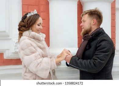 The bride and groom hold hands and look at each other on a winter day.