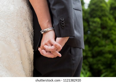 Bride and groom hold hands at outdoor wedding ceremony