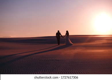 The bride and groom hold hands in the sandy desert at sunset, a beautiful wedding dress, long shadows, the wedding couple enjoys each other, a beautiful woman, a guy and a girl walk along the dunes