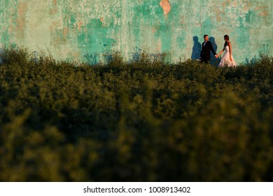 Bride and groom hold hands and walk together in front of old building with shingles
