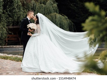 Bride and groom holding beautiful wedding bouquet. Bride letting her veil flutter in the wind, romantic photo. Beautifully fluttering veil. Happy bride and groom with a bride for a walk