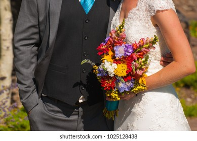 Bride and groom holding bouquet after wedding ceremony.