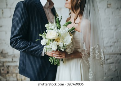 the bride and groom are holding a bouquet of white flowers and greenery in the background Vintage wall of white brick