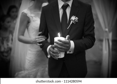Bride and groom holding candle. Close-up shot of hands