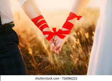 Bride and groom holding hands bounded with a red thread