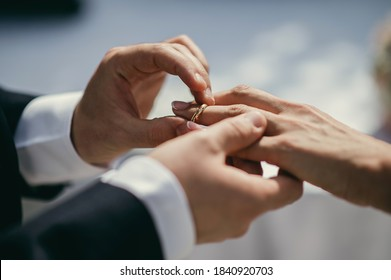 Bride and groom holding hands. Closeup couple exchanges wedding rings during ceremony. Wedding, union, loyalty concept.