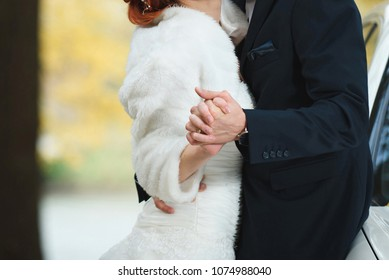 bride and groom holding hands and dancing in park
