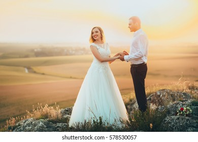 Bride and groom holding hands in mountains at sunset