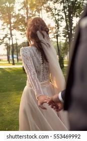 Bride & groom holding hands in nature