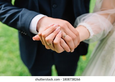 bride and groom holding hands with rings