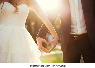 bride and groom holding hands in the shape of heart