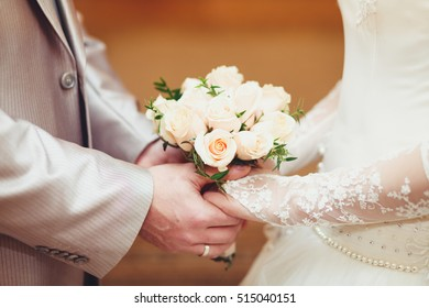 Bride and groom holding hands standing opposite each other, in the hands of a wedding bouquet