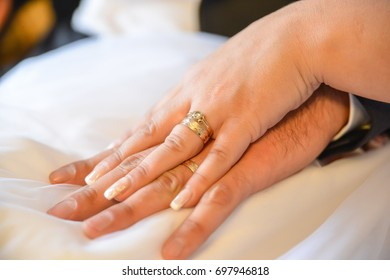 bride and groom holding hands together. wedding rings visible