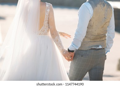bride and groom holding hands and walking in sunlight