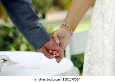 Bride and groom holding hands while saying their wedding vowels.
