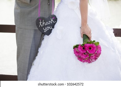 A bride and groom holding a heart shaped thank-you sign.
