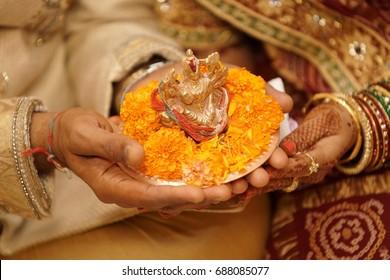 Bride & groom holding Indian Hindu idol in hands