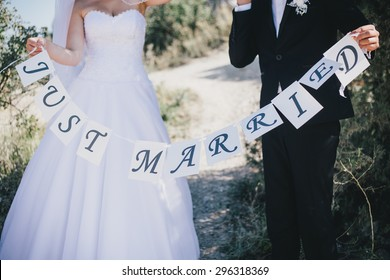 """Bride and groom holding """"Just married"""" sign. Wedding day"""