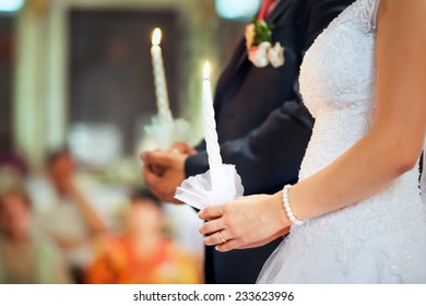 Bride and groom are holding lighted candles at the wedding ceremony in the church. Hands close-up shot