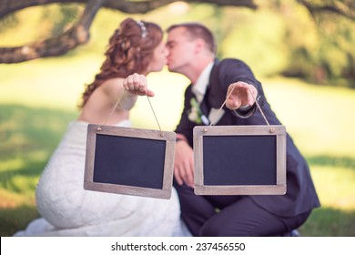 bride and groom holding two empty wooden signs while kissing