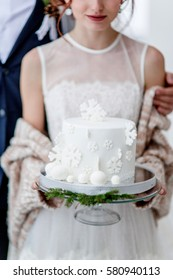 bride and groom holding winter wedding cake