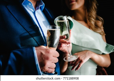 The bride and groom holds a glass of champagne and stand in the room. Close up. Holiday. Look at the glasses.