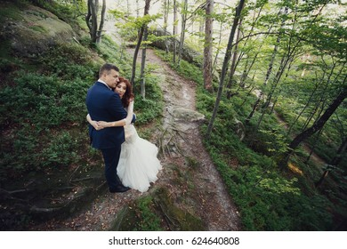 Bride and groom hug each other tender standing in the bright forest