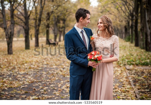 Bride and groom hugging in a forest in the autumn forest, wedding walk