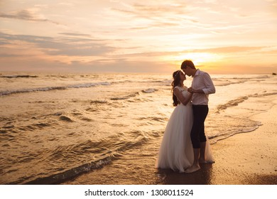 Bride and groom hugging and hold each other's hands at beautiful sunset background. Newlyweds at wedding day on ocean beach. Concept marriage, just married