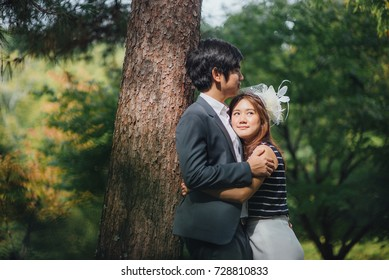 Bride and groom hugging under the tree in the nature