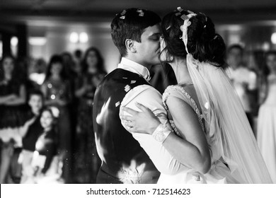 Bride and groom kiss each other tender after their first dance