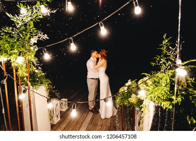 Bride and groom kiss at night on the background of wedding lights and decor