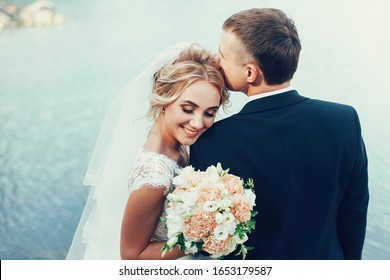 The bride and groom kiss on the background of the lake. Couple of lovers on the background of water. Classic wedding photography